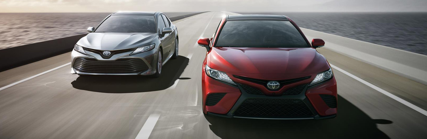 red and silver 2019 Toyota Camrys driving down highway