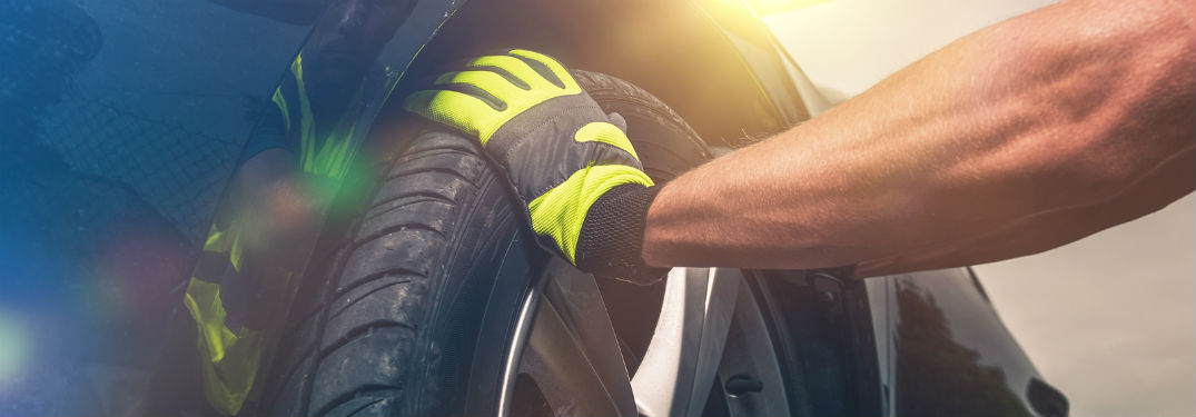 mechanic in gloves changing a tire