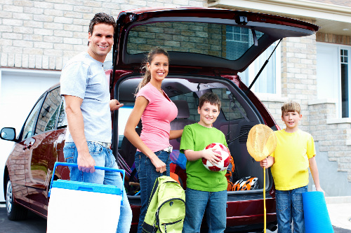 family of four packing their vehicle for a trip