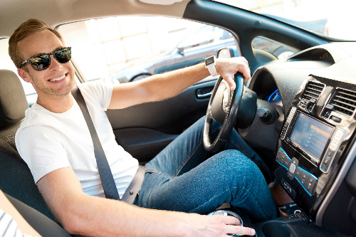 Man in sunglasses sitting in the drivers seat of a car