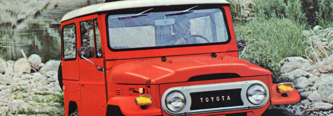 1974 Toyota Land Cruiser in red driving on rocky terrain