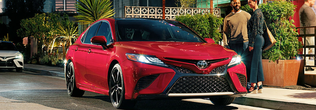 Couple standing next to a red 2019 Toyota Camry