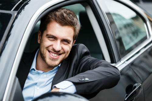 man in a suit sitting in a new car