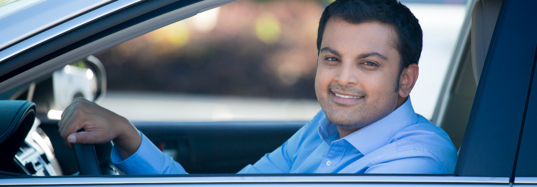 Man smiling behind the wheel of a sedan