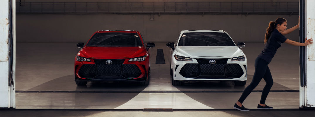 Woman pushing open garage with red and white 2020 Toyota Avalon models parked inside