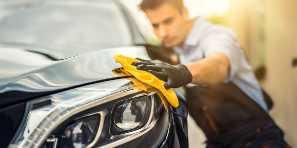 Man waxing the front of a vehicle with yellow cloth