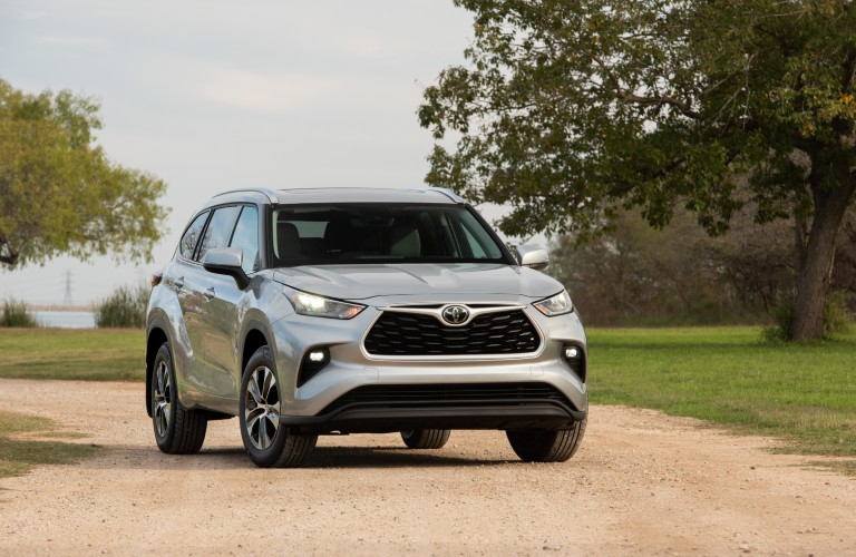 A head-on photo of the 2020 Toyota Highlander parked on a gravel road.