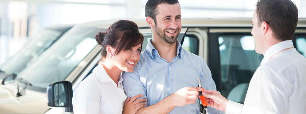 A stock photo of people getting the keys for their new car.