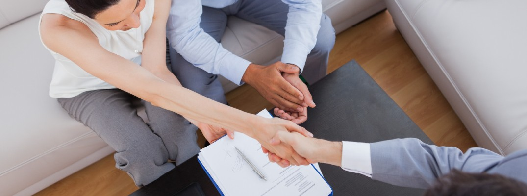 A stock photo of people shaking hands after completing paper work.