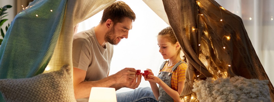 A stock photo of a dad spending time in a blanket fort.