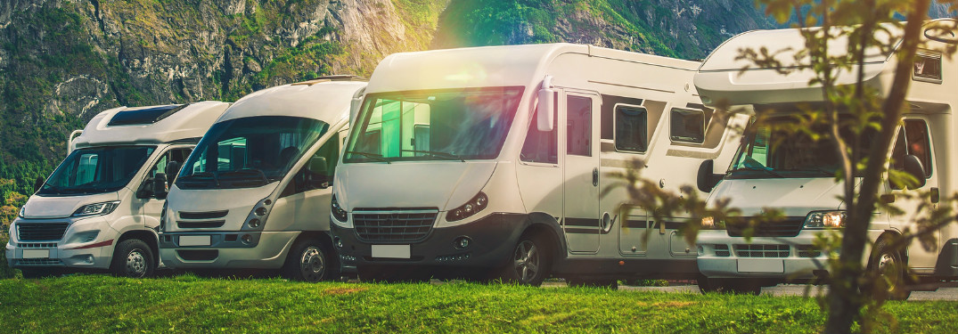 Four RVs Parked in Front of a Mountain