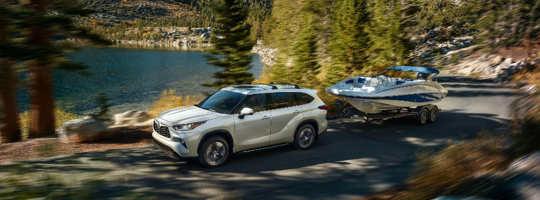 White 2020 Toyota Highlander towing boat