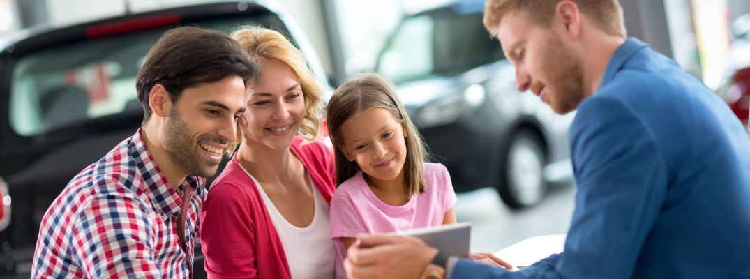 A stock photo of people looking at information in a car dealership.