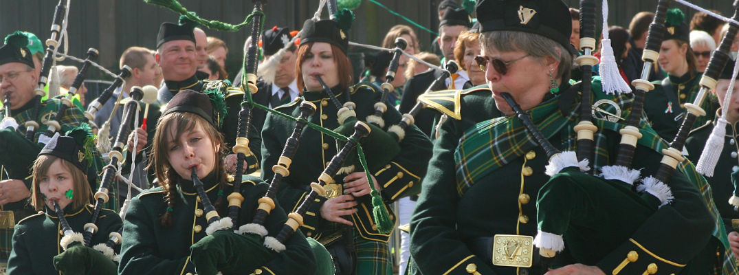 A stock photo of people playing bagpipes in a St. Patrick's Day parade.