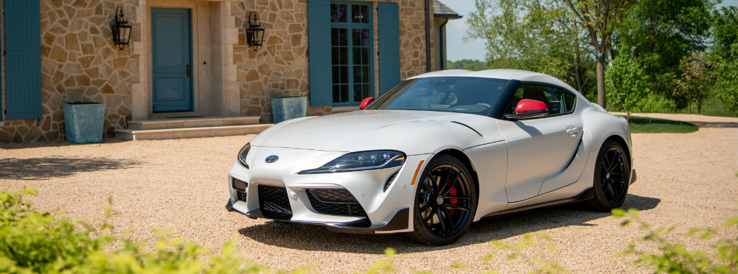 A front left quarter photo of the 2020 Toyota GR Supra parked in front a home.