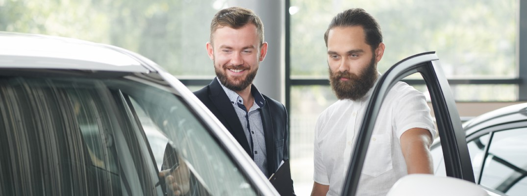 A stock photo of a person look at a vehicle with the help of a sales person.