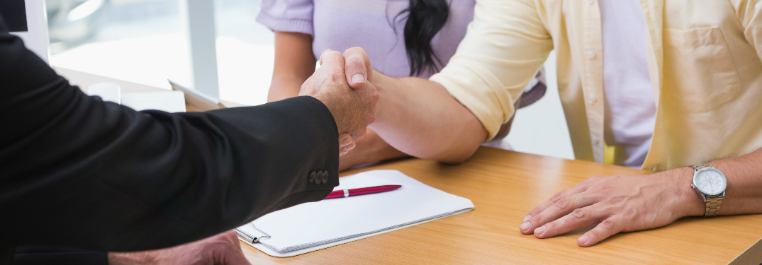 car salesman shaking hands with couple across desk