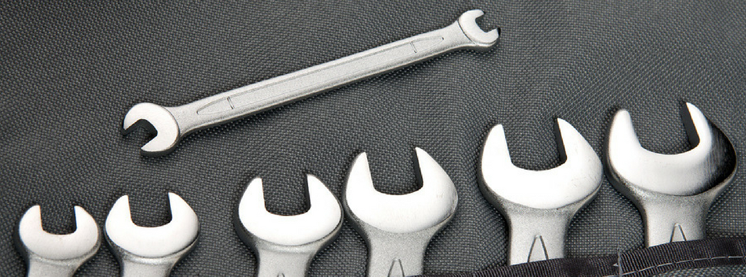Row of Wrenches with One Above