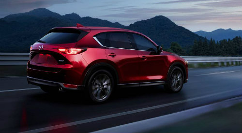 Red 2019 Mazda CX-5 driving on mountainous road