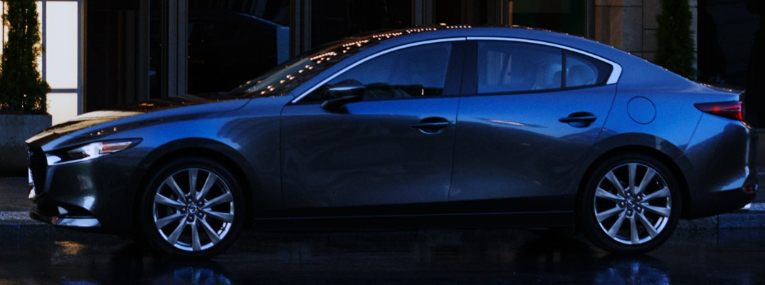 Profile view of blue 2019 Mazda3 parked on rainy city street