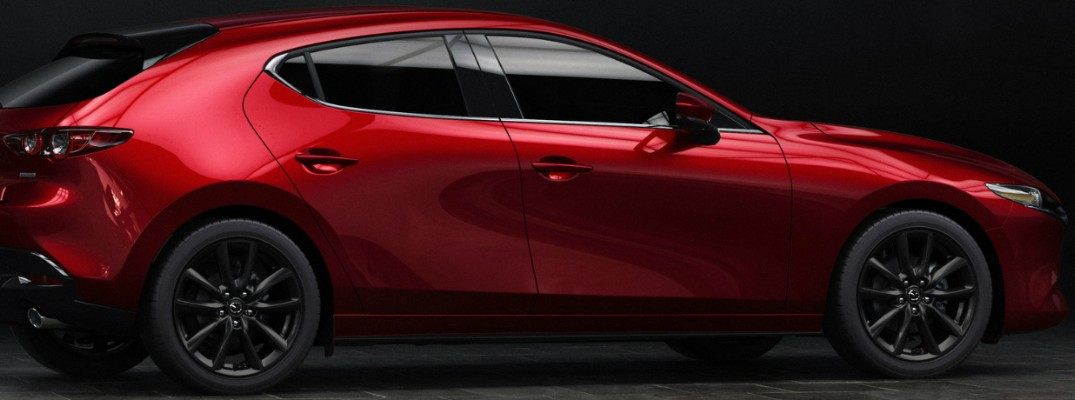 Profile view of red 2019 Mazda3 hatchback on black background
