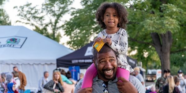 Father with daughter on his shoulders at festival