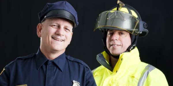 Police man and firefighter smiling in front of black background