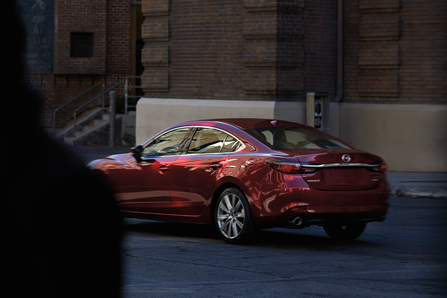 Rear driver angle of a red 2019 Mazda6 with a person walking in front on left side