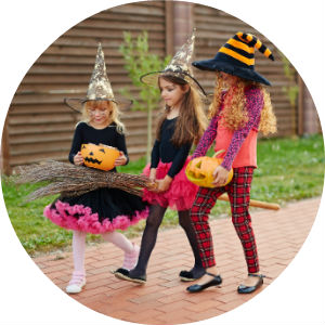 Three girls trick or treating dressed as witches