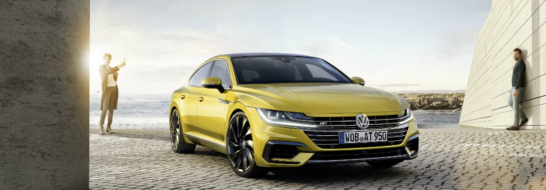 yellow volkswagen arteon parked, people in background