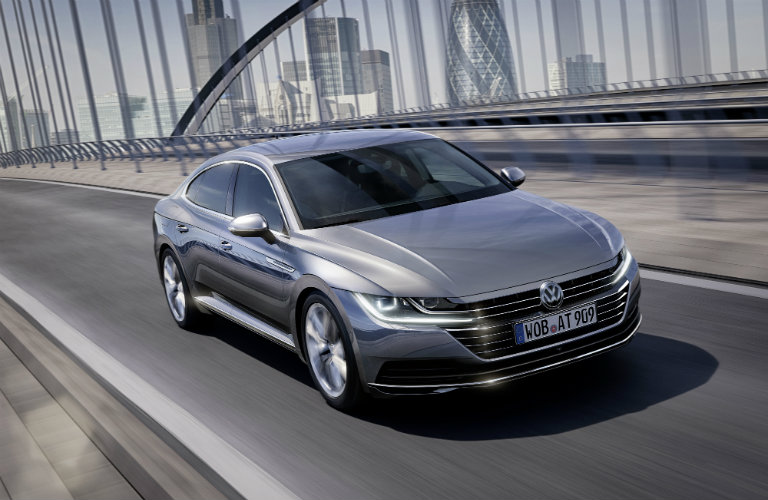 silver volkswagen arteon driving on bridge