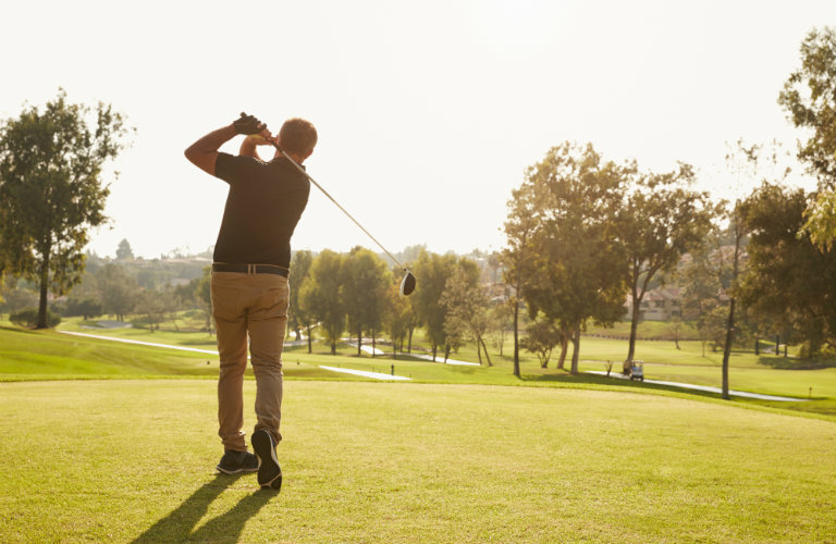 man holding golf swing after drive