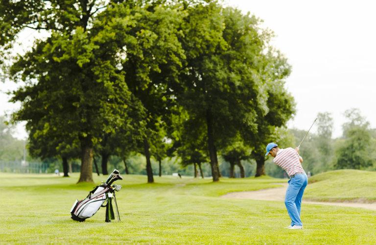 man golfing alone