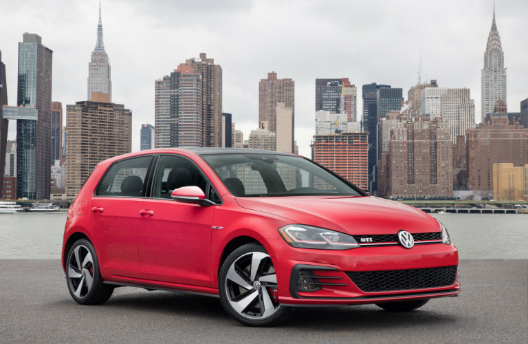 red volkswagen golf in front of Manhattan skyline
