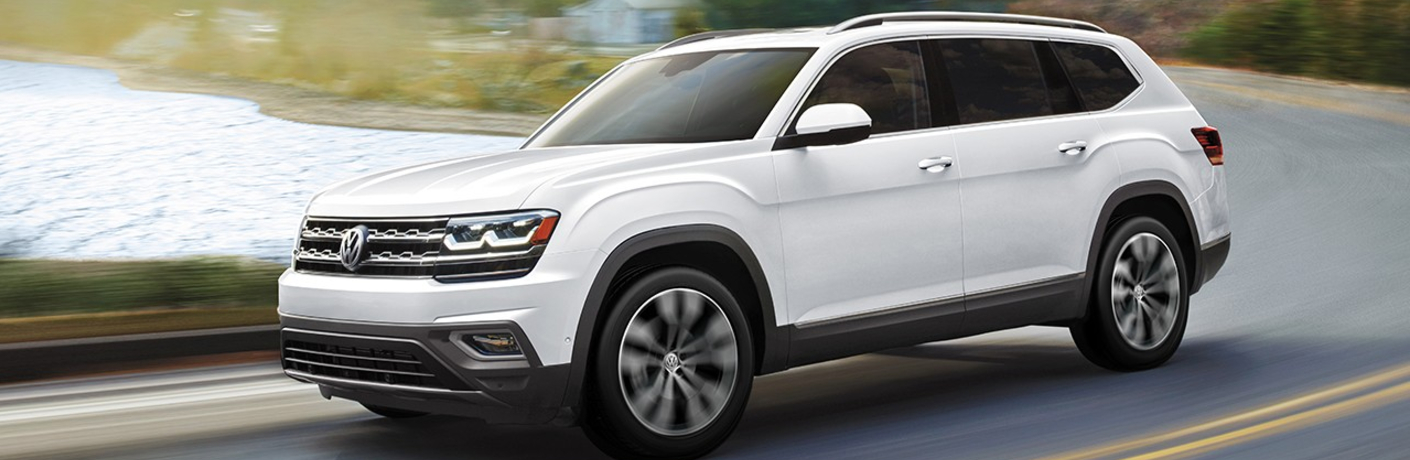 A white 2020 Volkswagen Atlas driving down an open road.