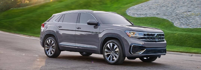 A gray 2020 Volkswagen Atlas Cross Sport driving down a road.