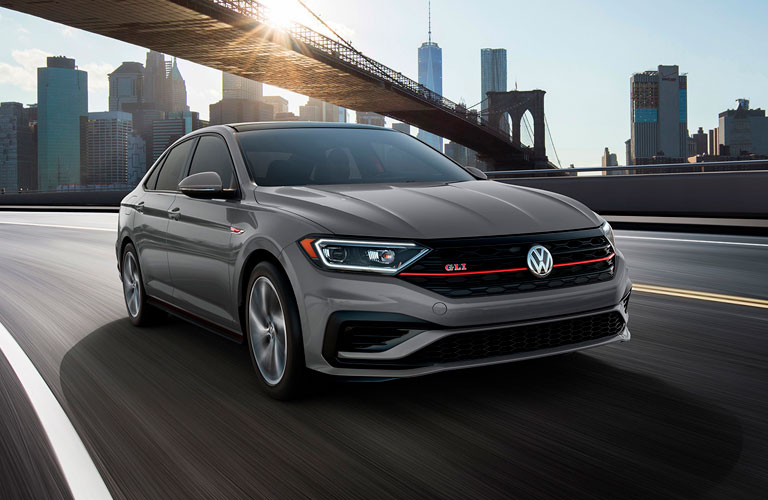 A front view of a gray 2020 Volkswagen Jetta GLI driving down an open city freeway.