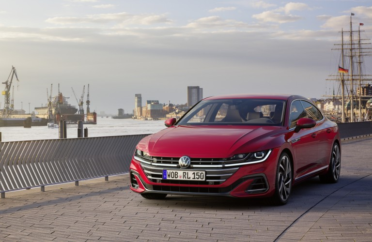 The front image of a red 2021 Volkswagen Arteon parked near water.