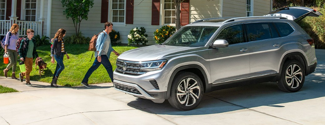 A gray 2021 Volkswagen Atlas parked at a house with the family walking towards it.