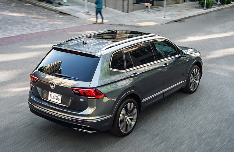 The rear and side view of a dark gray 2021 Volkswagen Tiguan.