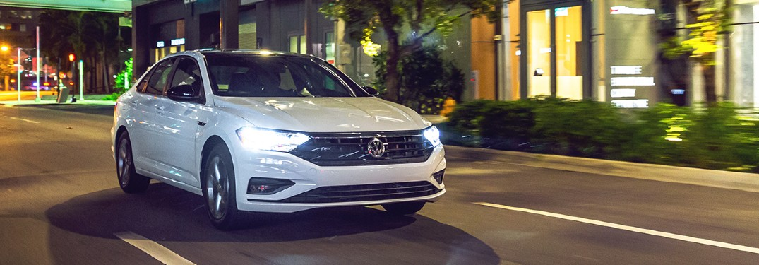 The front view of a white 2021 Volkswagen Jetta driving at night.