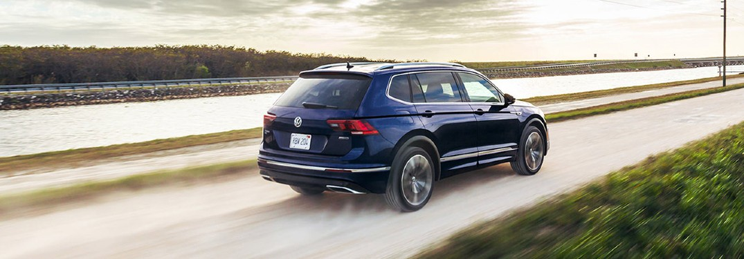 The rear and side view of a dark blue 2021 Volkswagen Tiguan driving down an empty road.