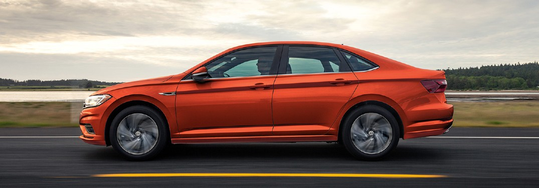 The side view of an orange 2021 Volkswagen Jetta driving down a road.