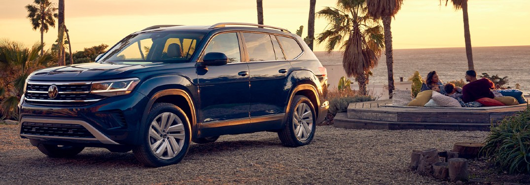 The front and side view of a blue 2021 Volkswagen Atlas parked in front of a couple laying and watching the sunset on a beach.