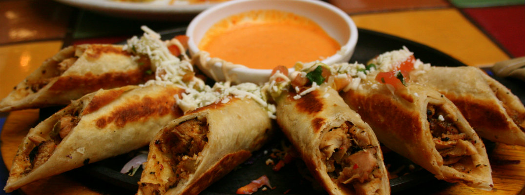 a plate tray of rolled chicken tacos with cheese dipping sauce at a mexican restaurant for cinco de mayo