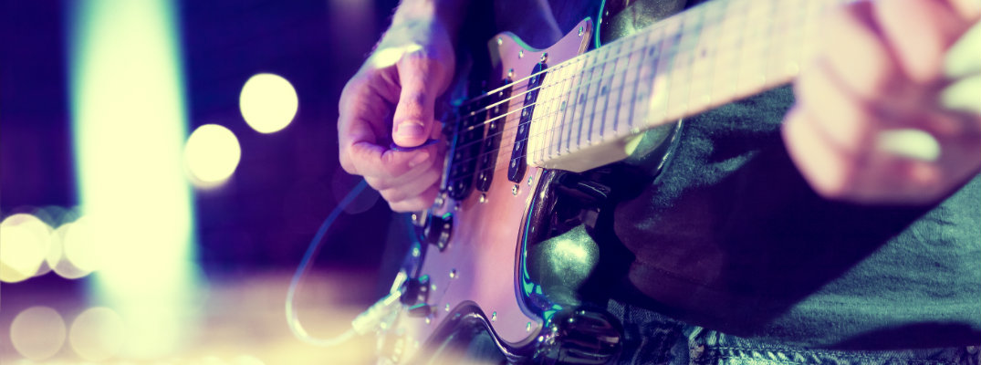 close up of a man strumming and playing an electric guitar on stage