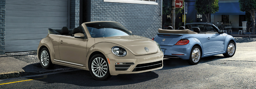 Two 2019 VW Beetle Final Edition Convertible Vehicles Parked in Front of a Blue Building