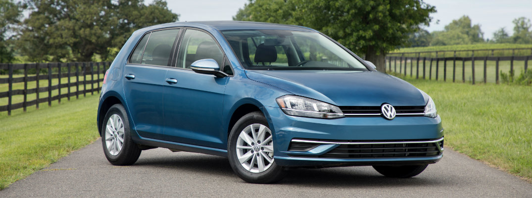 2018 Volkswagen Golf aqua teal exterior shot parked in the middle of a country road surrounded by green grass and wooden fences