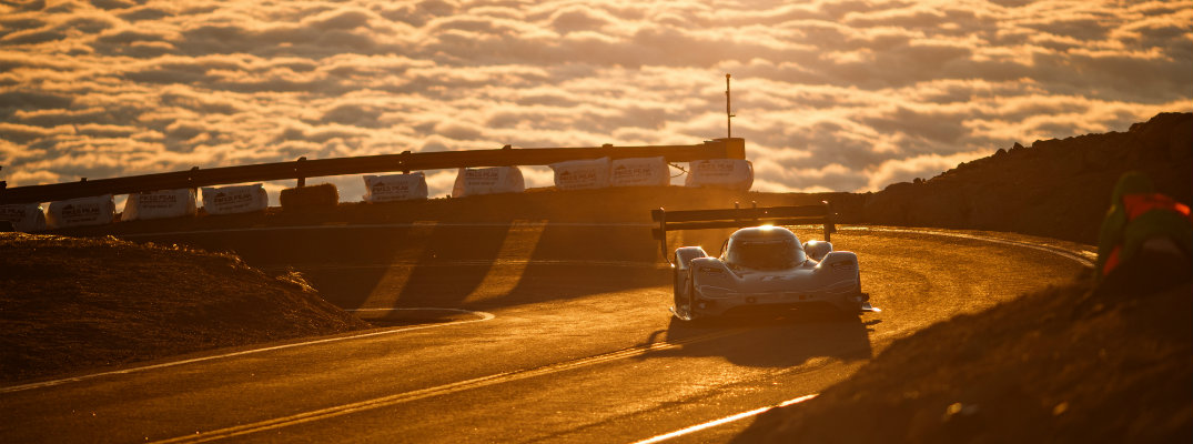 Volkswagen I.D. R Pikes Peak exterior shot climbing the peak with a sea of clouds and setting sun in the background