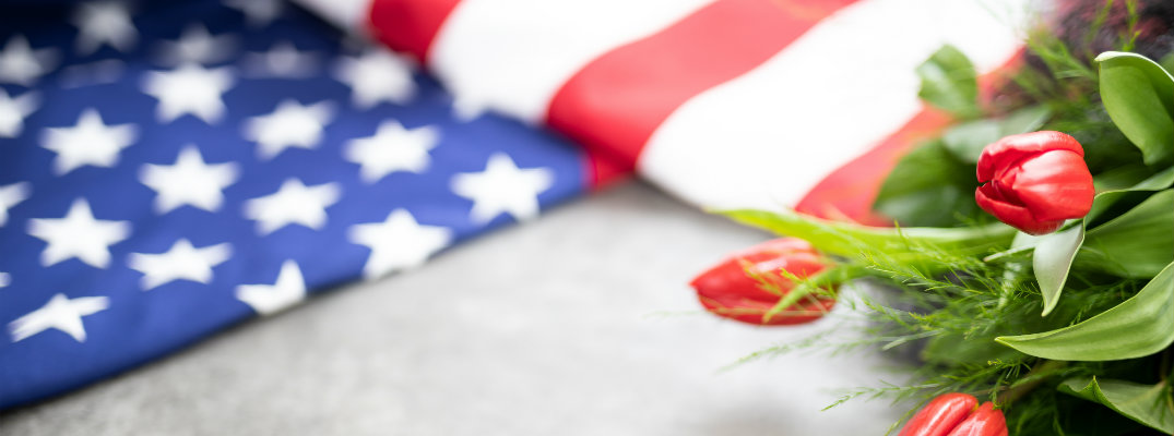 a folded American flag on the ground next to a bushel of red tulips